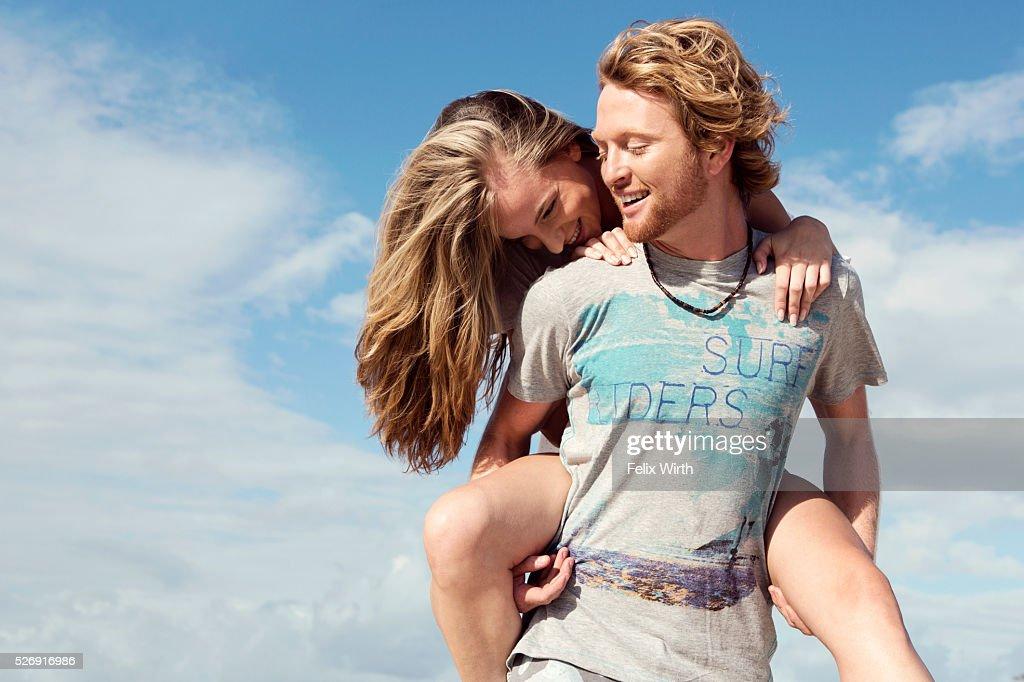 Young man giving woman piggyback ride : Stock-Foto