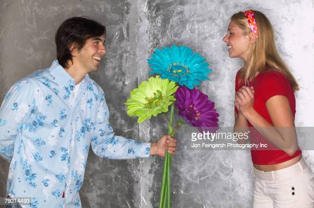 Young man giving young woman large flowers