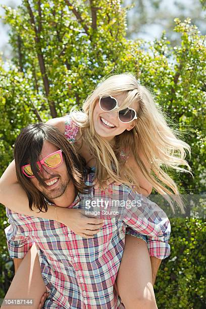 Young man giving young woman piggyback