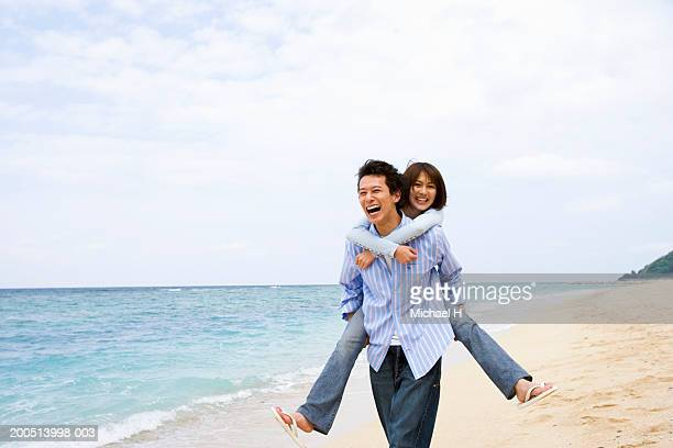 Young man giving young woman piggyback ride on beach