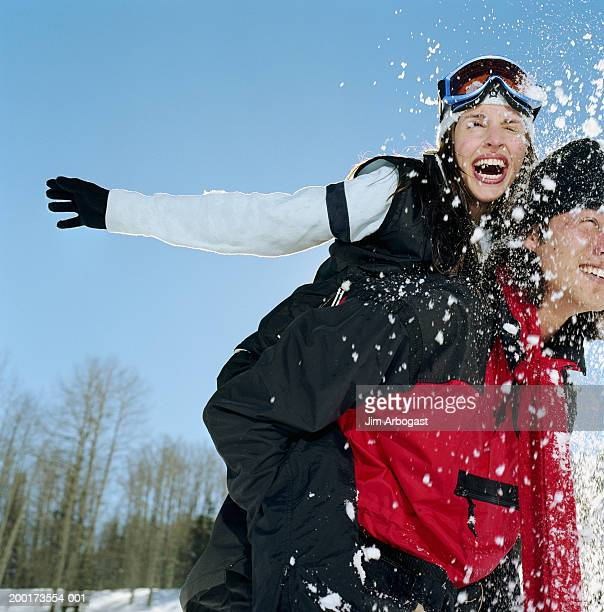 Young man giving young woman piggyback ride, snowball hitting woman