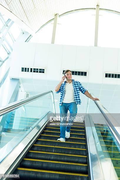 Junger Mann gehen mit der Rolltreppe in Dubai