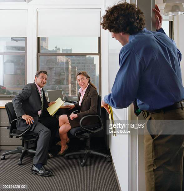 Young man greeting two businesspeople meeting