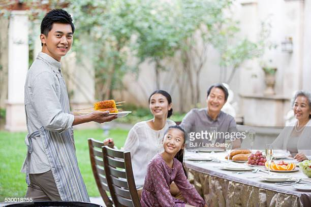 Young man grilling corns for his families