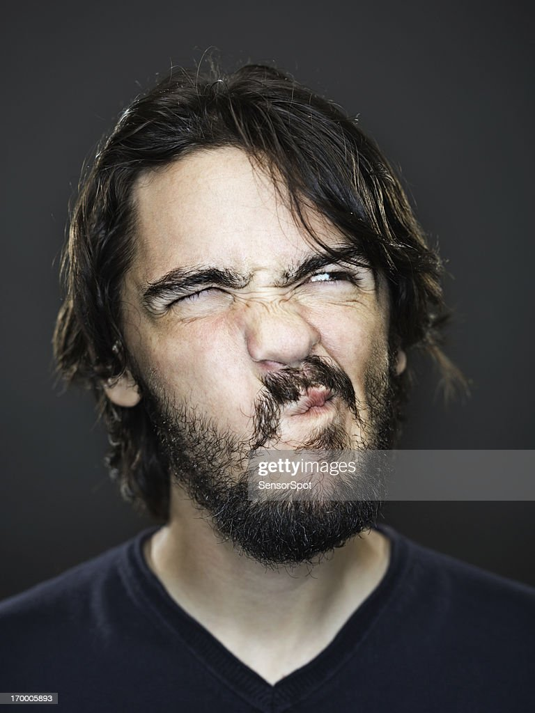 Young man grimacing : Stock Photo