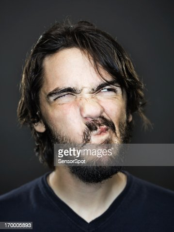 Young man grimacing