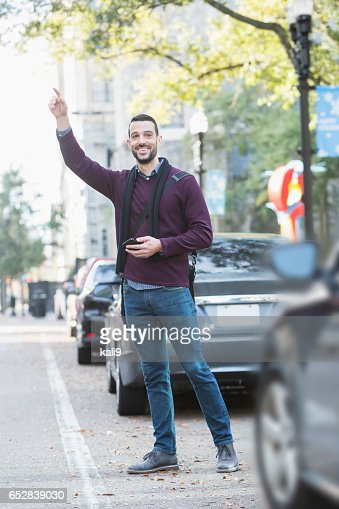 Young man hailing taxi on city street : Stockfoto