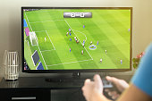 Young man hanging out and playing imaginary soccer or football video game with console and tv. Holding controller in hand. Fun freetime activity.