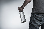 Close up of hand of male alcoholic holding bottle of harmful beverage. He is standing and turning back to camera. Isolated and copy space in left side