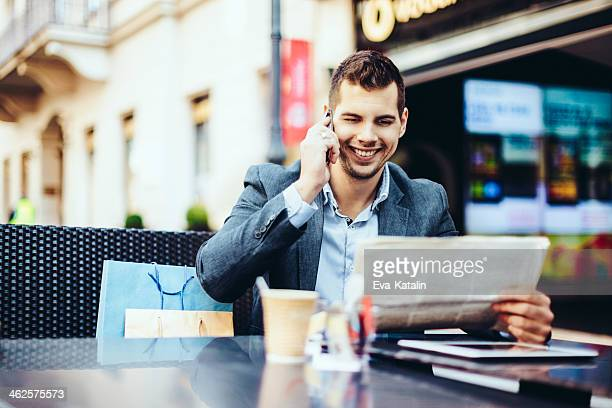 Young man having a break and reading newspaper