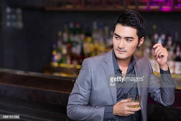 Young man having a drink at bar