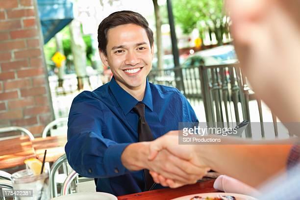 Jeune homme ayant une réunion d'affaires dans le café en plein air