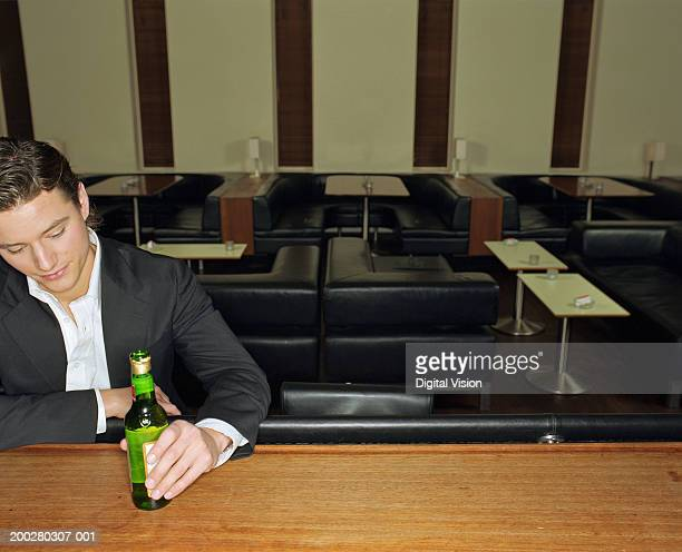 Young man having drink, resting elbow on bar