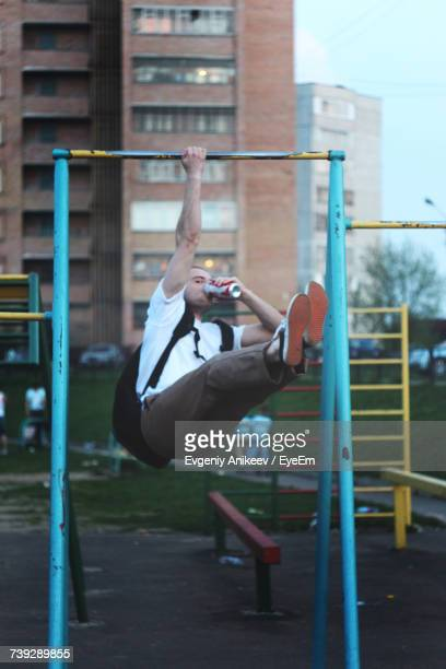 Young Man Having Drink While Hanging On Outdoor Play Equipment