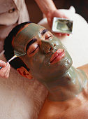 Young man having facial mask in beauty parlour, close-up, elevated view