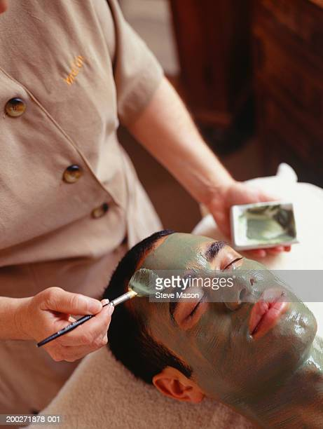 Young man having facial mask in beauty parlour