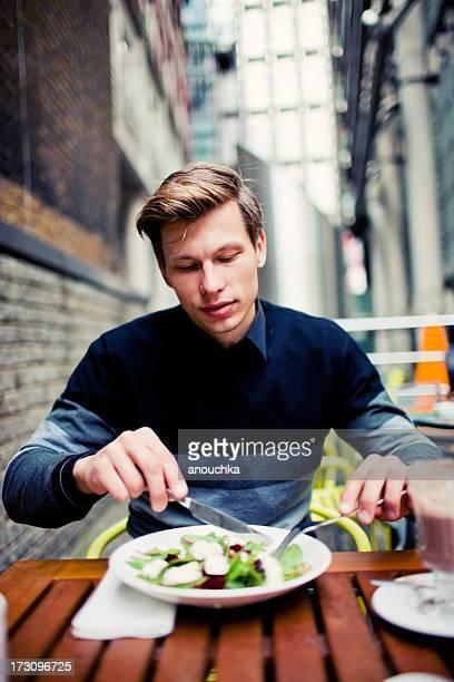 Hombre joven con almuerzo saludable en el café al aire libre
