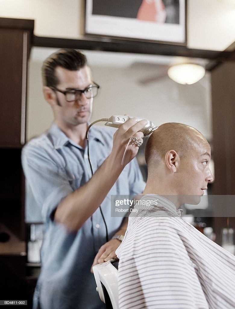 Young man having his head shaved by barber : Stock Photo