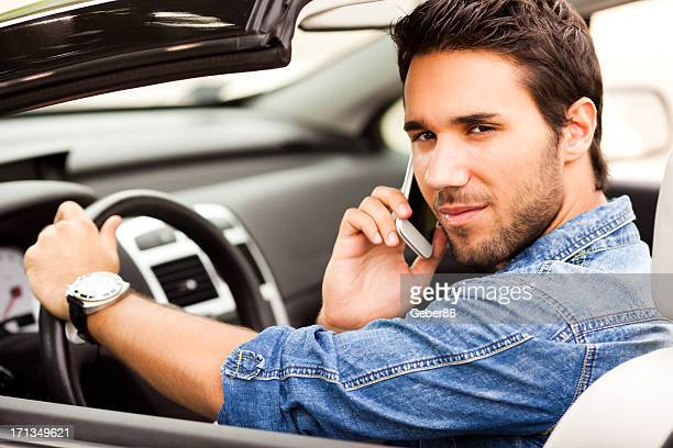 Young man having phone conversation in his car