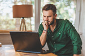 Young man having stressful time working on laptop