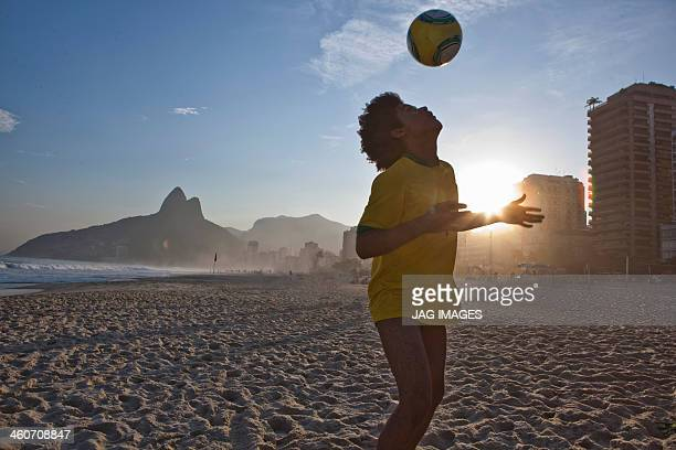 Young man heading football, Ipanema Beach, Rio, Brazil