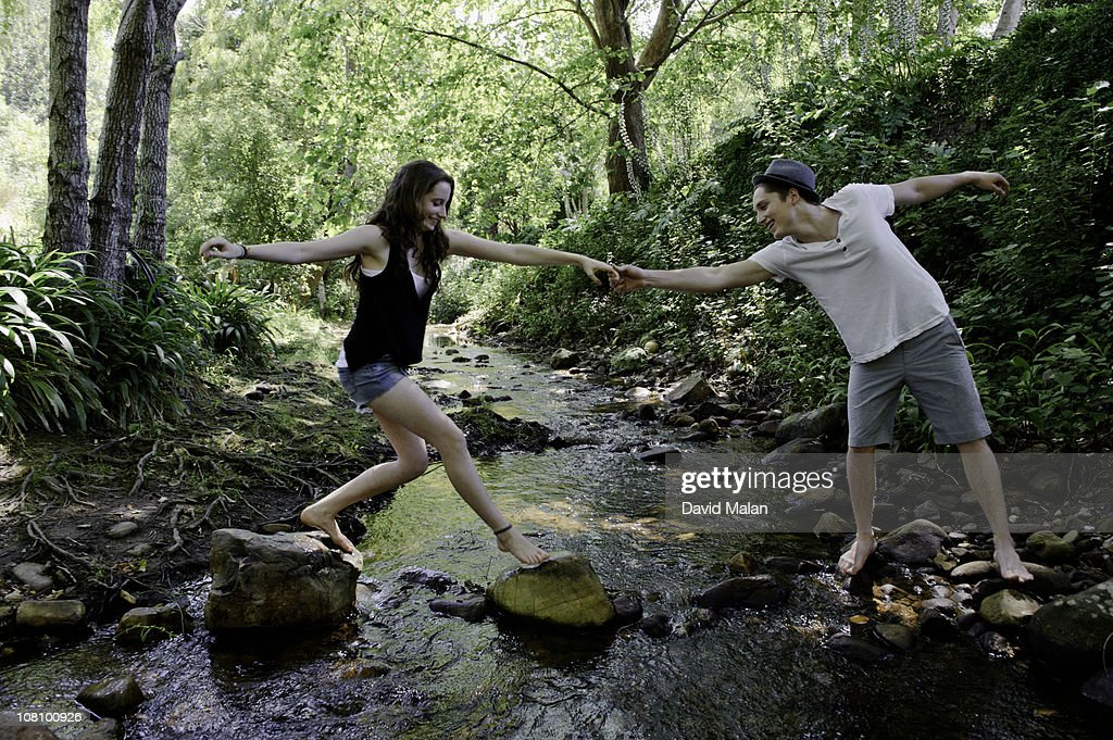 Young man helping a girl cross a stream