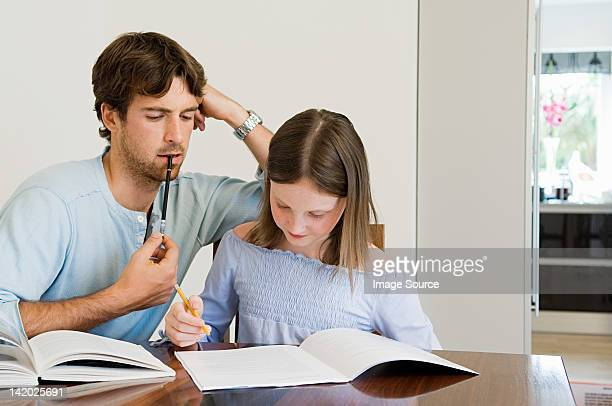 Young man helping daughter with homework