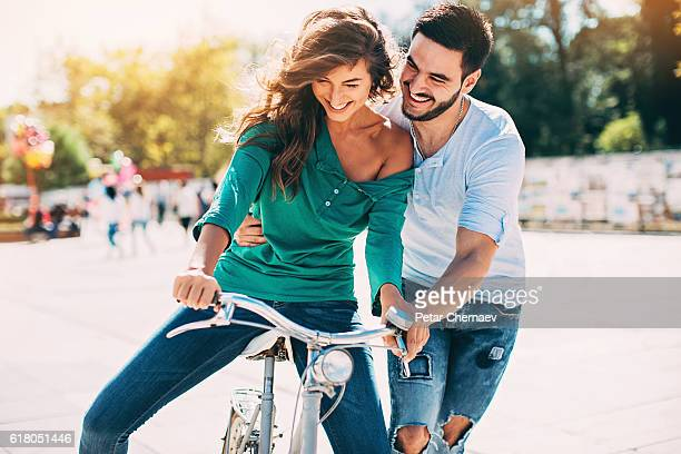 Young man helping his girlfriend to ride a bike