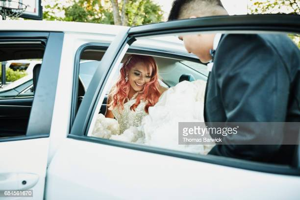 Young man helping smiling young woman in quinceanera gown into car