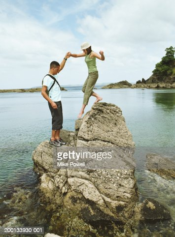 Young man helping woman climb down from rock on beach