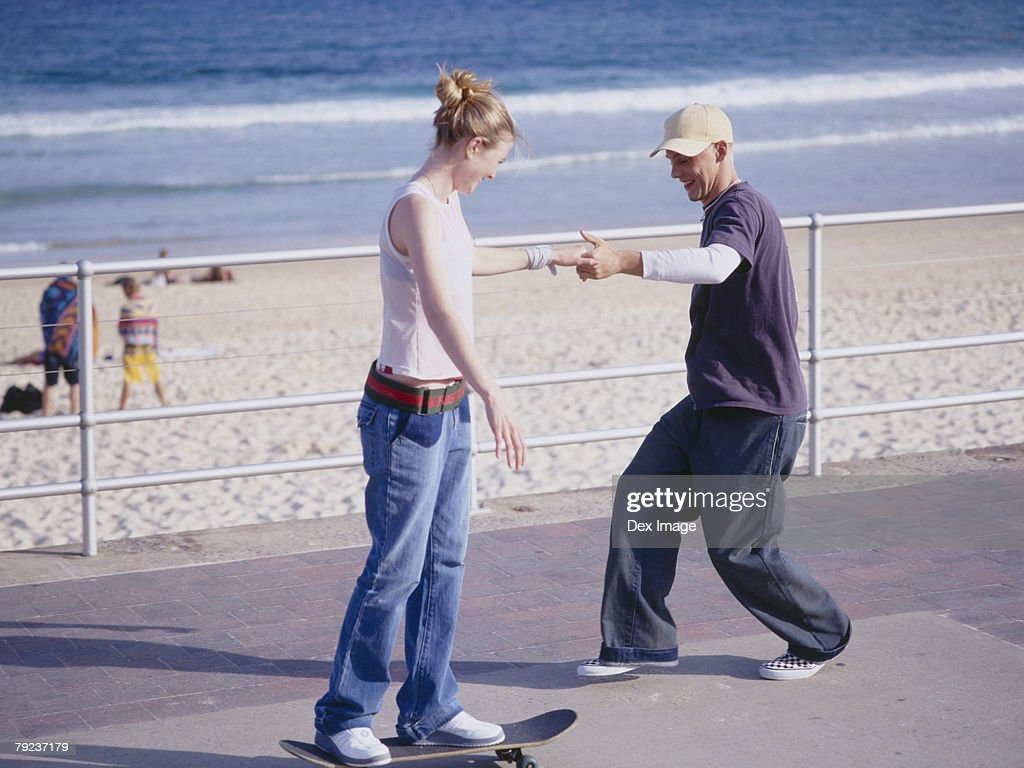 Young man helping young woman balancing on skateboard : Stock Photo