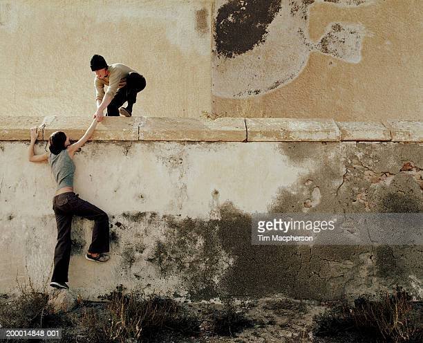 Young man helping young woman over wall