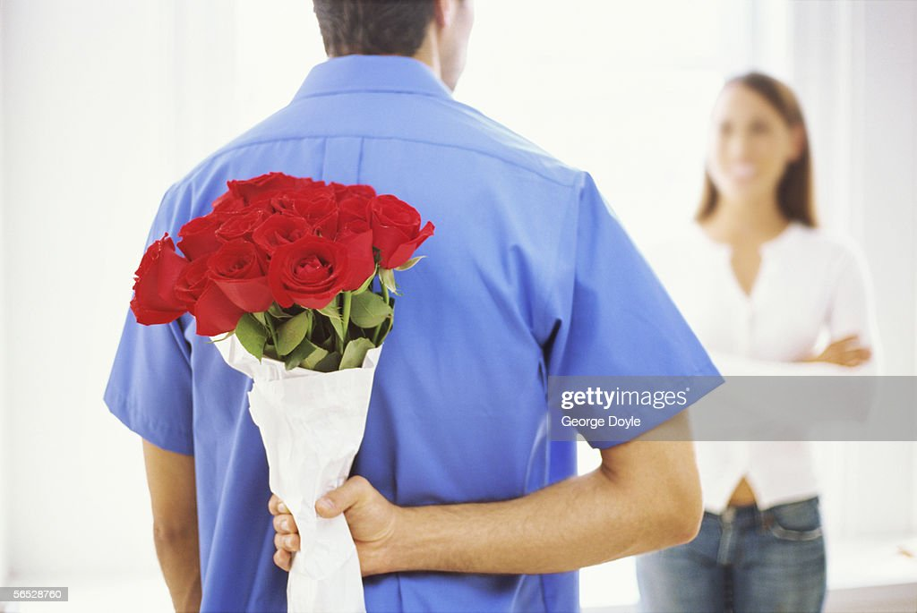 young man hiding a bunch of flowers : Stock Photo