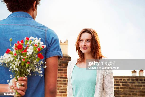 Young man hiding flowers behind back for woman