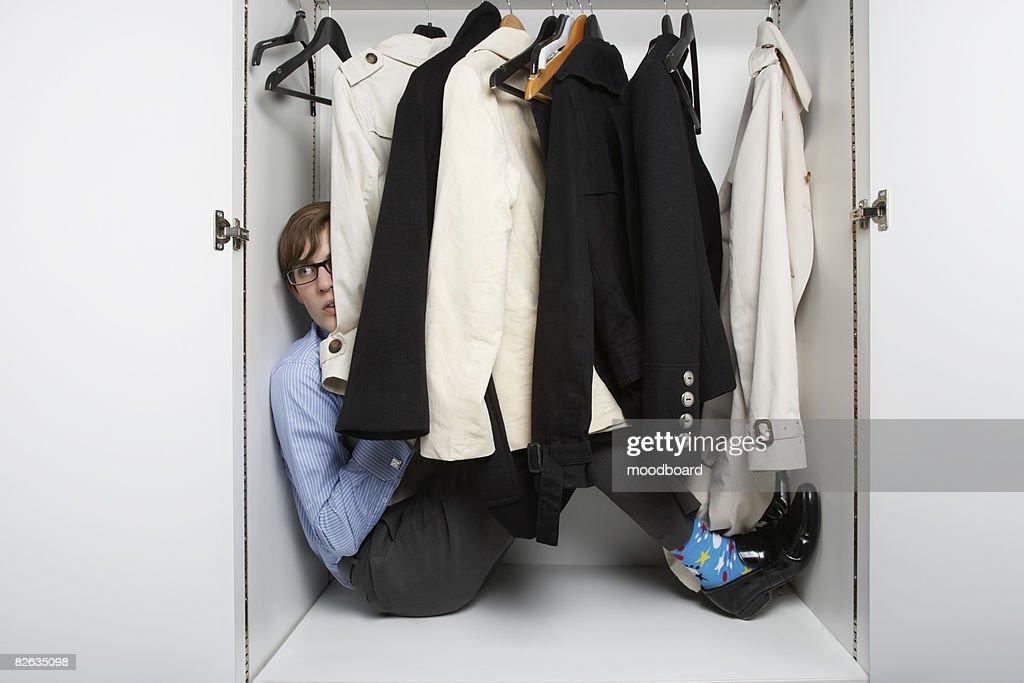 Young man hiding in wardrobe behind clothes