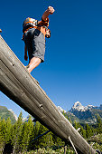 A young man hiker balances on an old log in the Grand Teton National Park, Wyoming.