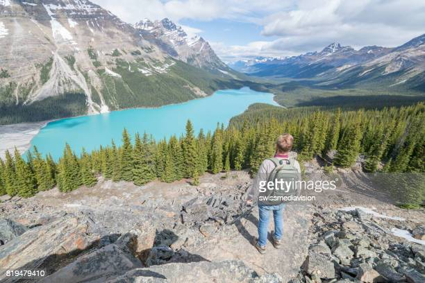 Young man hiker on rock above mountain lake