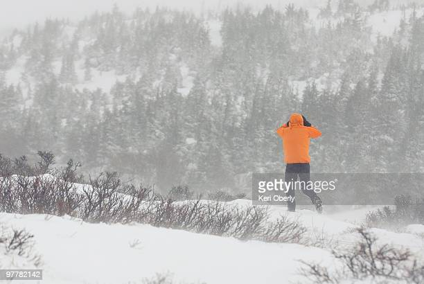 A young man hikes on a trail during a whiteout storm in Anchorage, Alaska.