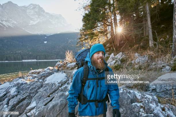 Young man hiking by Lake Eibsee in winter, Zugspitze, Bavaria, Germany