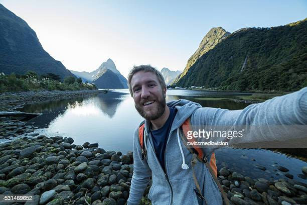Young man hiking, captures selfie in Milford sound