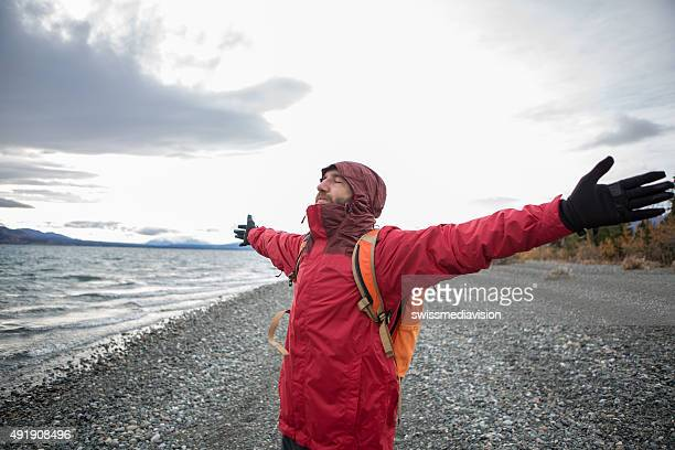 Young man hiking enjoying freedom in nature-Winter