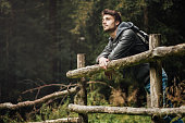 Young man with backpack hiking in the forest and leaning on a wooden fence, nature and physical exercise concept