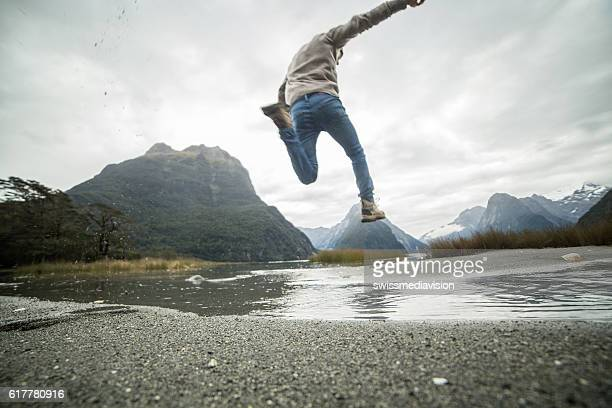 Young man hiking jumps over the mountain river