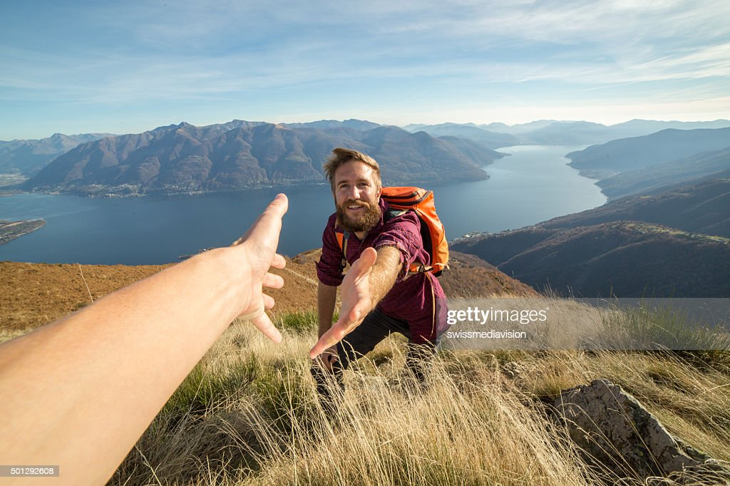 Young man hiking pulls out hand to get assistance : Stock Photo
