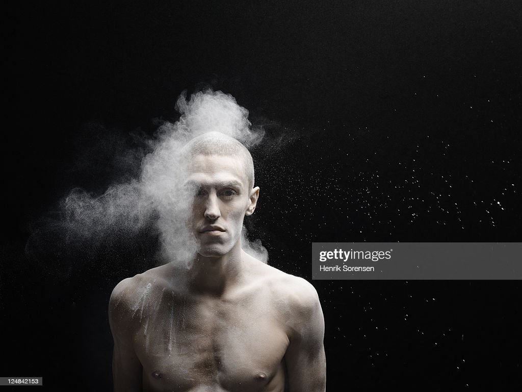 young man hit by cloud of white powder : Stock Photo