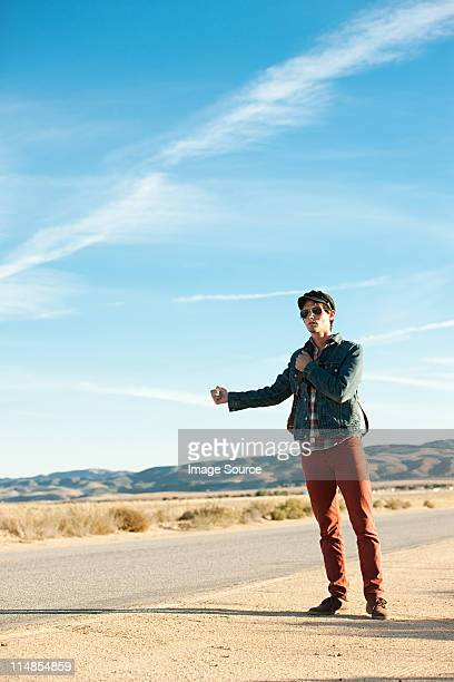 Young man hitchhiking at roadside