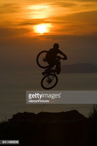 A young man hits a big jump on his mountain bike at the end of the day as the sun sets on the ocean.