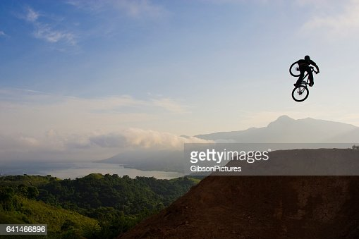 A young man hits a big jump on his mountain bike early in the morning.
