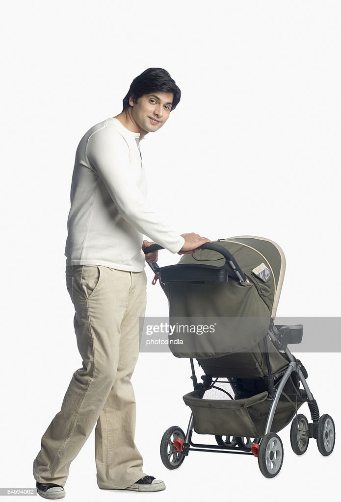 Young man holding a baby stroller : Stock Photo