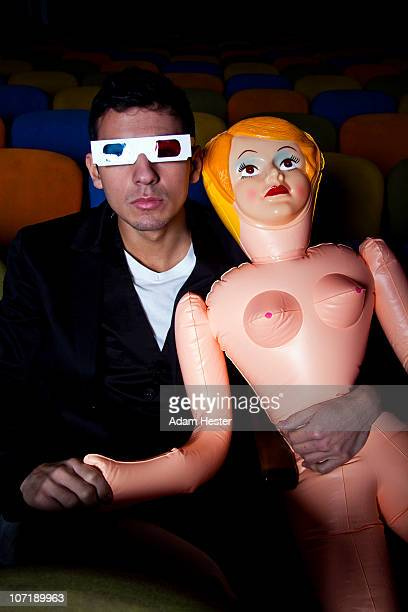 A young man holding a blow up doll in a theater.